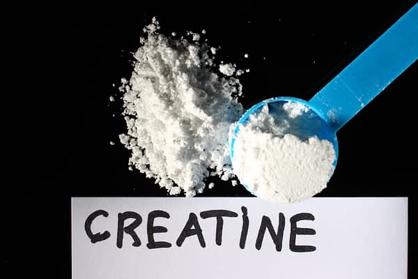 A blue scoop is holding white powder and the words say creatine