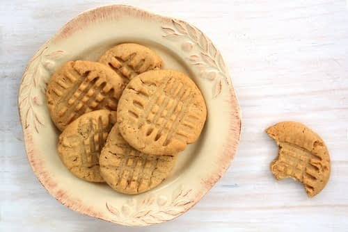 5 Peanut Butter Keto Cookies are on a nice pink and ivory plate. A cookie with a bite out of it is nearby on the table