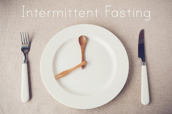 Intermittent Fasting is written as a banner above a plate with spoon and fork on a plate as if it were a clock timing the fasting window, then a fork and knife and set next to the large white plate