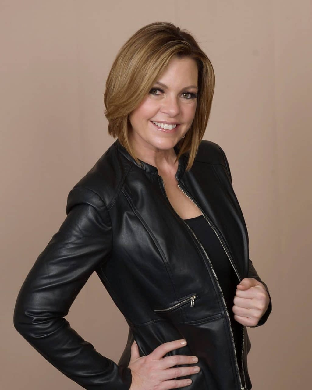 Lori Ballen Keto coach is standing confidently with her leather jacket